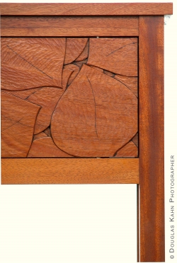 The surface of this cabinet door is lively with chisel strokes.
