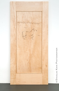 A Carved Horse trots across a door panel.